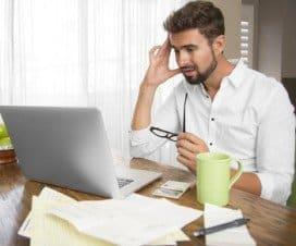 zmartwiony mężczyzna wpatruje się w komputer
