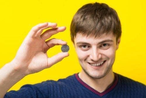 mężczyzna trzyma monete