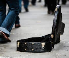 Otwarty futerał gitary, do którego zostały wrzucone drobne
