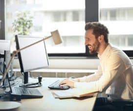 Mężczyzna w białek koszuli pracuje przy laptopie