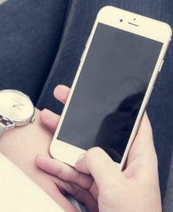 Kobieta trzyma w dłoni telefon komórkowy