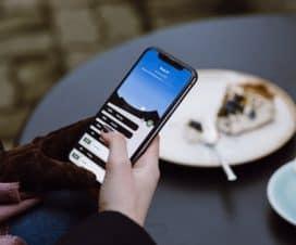 Kobieta w kawiarni używa telefon komórkowy