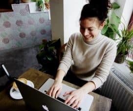 Kobieta pracuje przy laptopie apple