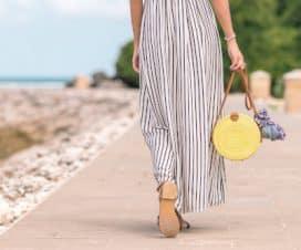 Kobieta w sukience w paski spaceruje nad morzem