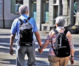 Starsze małżeństwo idzie po mieście z plecakami