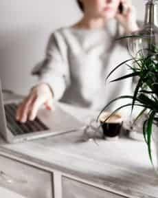 Kobieta rozmawia przez telefon przy laptopie