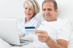 małżeństwo z laptopem i kartą płatniczą