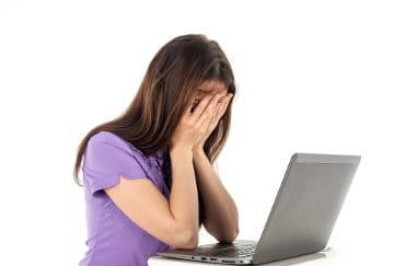 Kobieta zmartwiona siedzi przy laptopie zakrywa twarz dłońmi