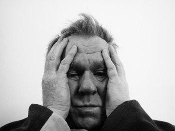 Starszy zmartwiony mężczyzna przykłada dłonie do głowy