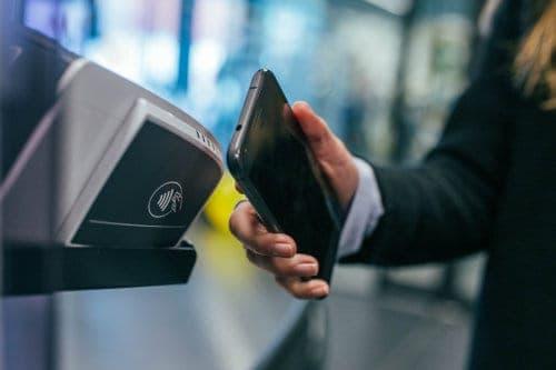 Kobieta dokonuje płatności zbliżeniowej telefonem komórkowym