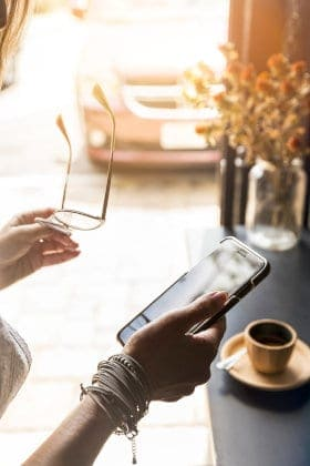 Kobieta trzyma w dłoniach telefon komórkowy i okulary