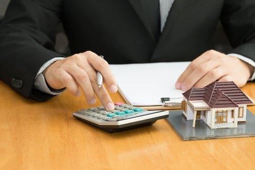 obliczenia na kalkulatorze i miniatura domu jednorodzinnego