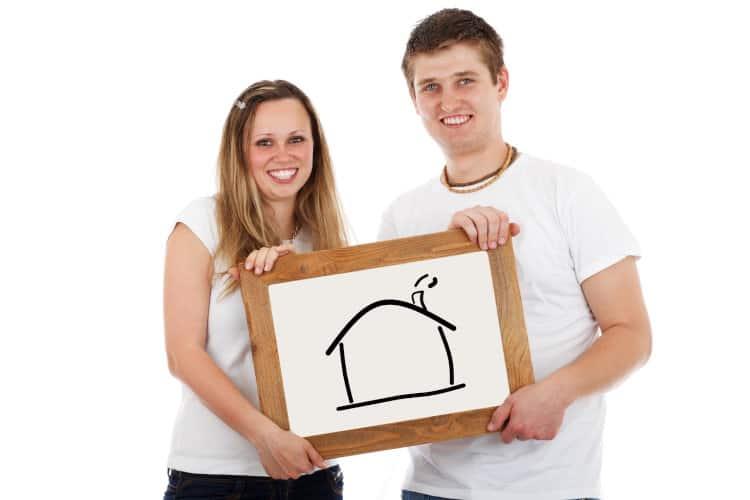 Młodzi ludzie trzymają tablicę z rysunkiem domu