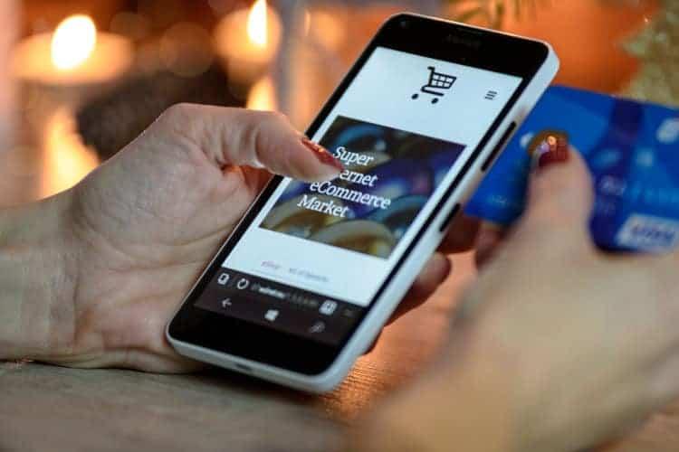 Kobieta trzyma w dłoni kartę kredytową i telefon komókowye