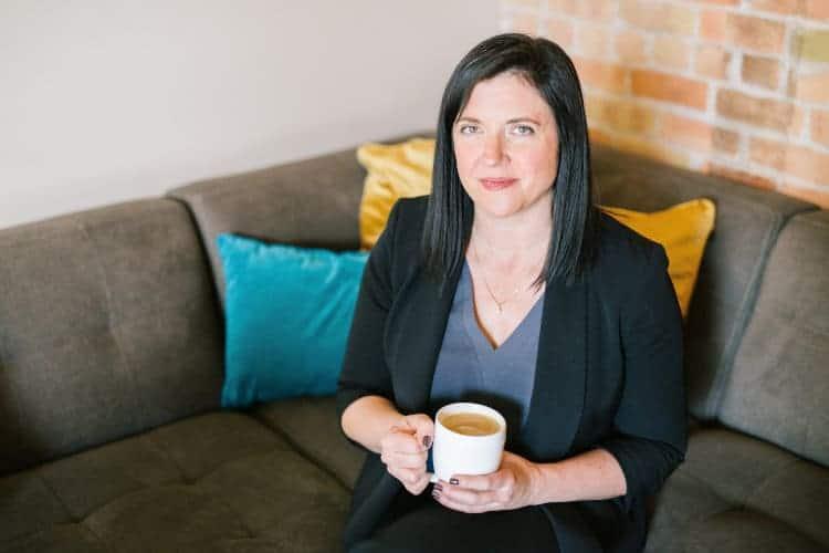 Kobieta siedzi na kanapie z kubkiem kawy