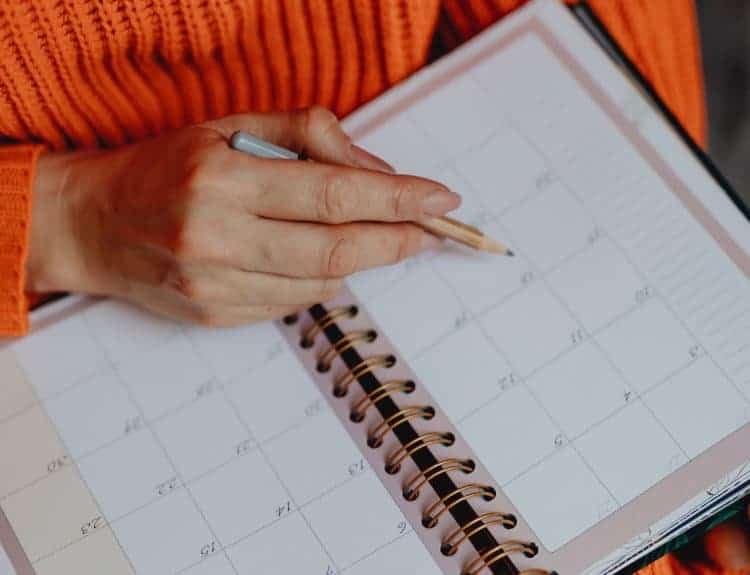 Kobieta zaznacza coś w kalendarzu