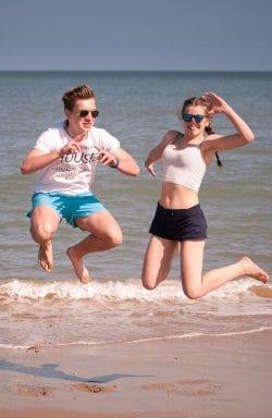Mężczyzna i kobieta skaczą przez fale